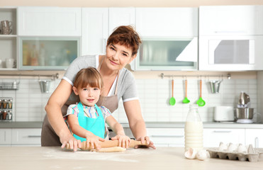 Cute little girl and her grandmother on kitchen