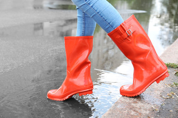 Woman in red rubber boots, outdoors