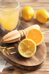 Fresh lemons and squeezer on wooden table