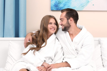 Young loving couple in bathrobes sitting on bed at home