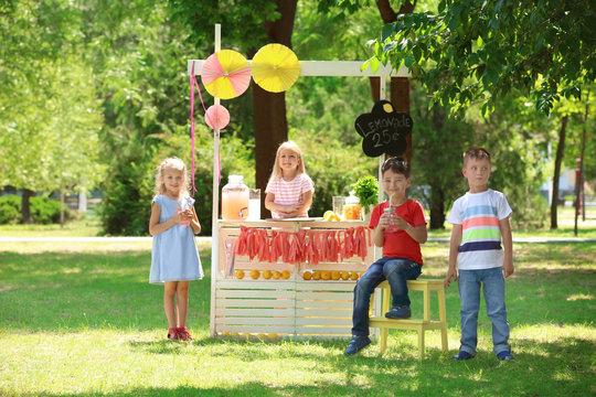 Happy children near lemonade stand in park