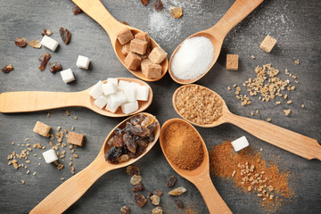 Various kinds of sugar in wooden spoons on grey table Wall mural