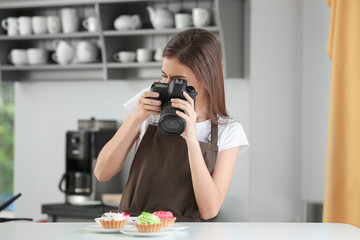 Young female blogger making photo of freshly cooked dish in kitchen