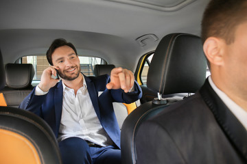 Handsome man talking on phone while sitting in taxi car Fototapete