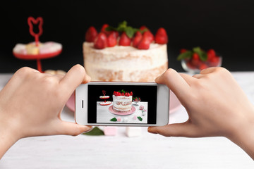 Blogger making photo of strawberry cake