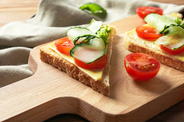 Tasty sandwiches with fresh cucumber on wooden board