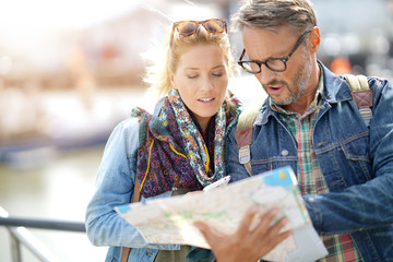 Couple of tourists reading city map and using smartphone