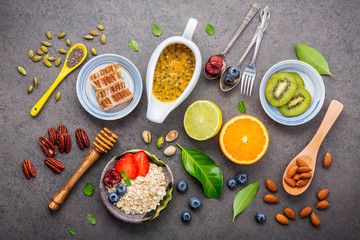 Ingredients for the healthy foods background Mixed nuts, honey, berries, fruits, blueberry, orange, almonds, oatmeal and chia seeds .The concept of healthy food set up on dark stone background.