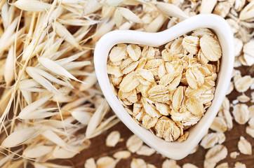 Oat groat in heart-shaped bowl, grain on oatmeal ears plants background