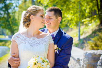 Wedding beautiful couple with good mood kisses on a nature. Love is all you need. Plus size tenderness bride and younger groom