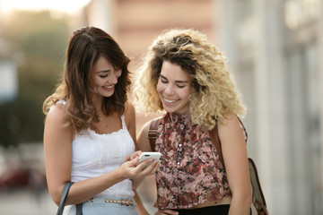 Happy women friends looks pictures in smartphone and giggling
