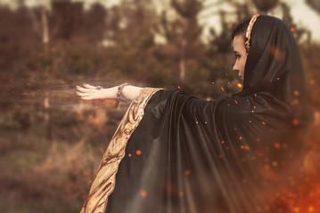 the witch in a black cloak uses magic