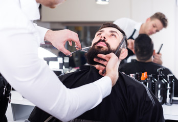 Handsome man forming beard of client into shape