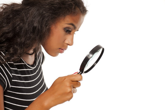 Beautiful young dark skinned woman looking trough the magnifying glass