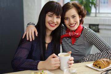 beste freundinnen umarmen sich in einem café
