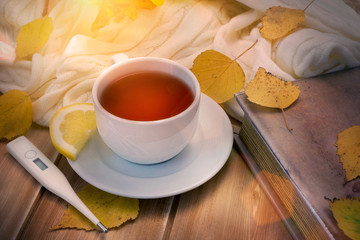Thermometer and tea with lemon in white cup and old book on a wooden table with autumn yellow leaves. Flu, cold concept