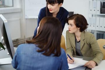 kolleginnen im büro schauen auf pc