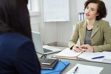 frauen unterhalten sich im büro am schreibtisch