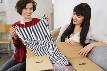 freundinnen packen ein paket mit mode aus