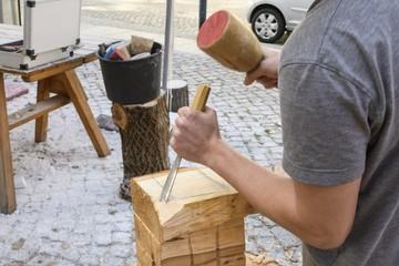 Holz wird mit Holzhammer und Stechbeitel bearbeitet