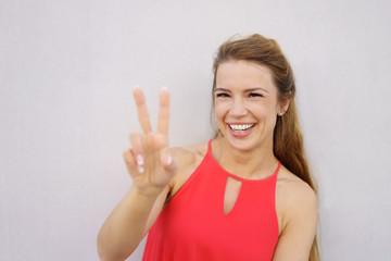 lachende frau zeigt das sieger-zeichen mit der hand