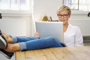 blonde frau sitzt mit ihrem, laptop am tisch und legt die füße hoch