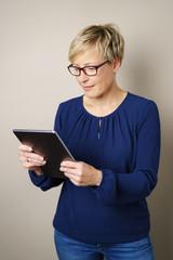 frau liest die nachrichten am tablet