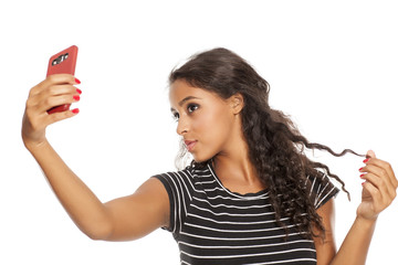 Young and beautiful dark skinned girl taking a selfies with her smartphone