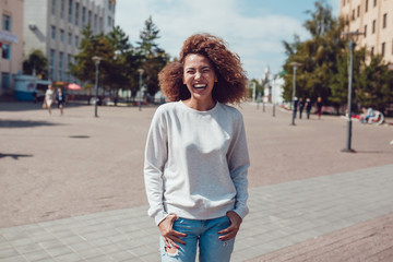 Curly haired girl with freckles in blank grey sweatshirt on the street. Mock up.