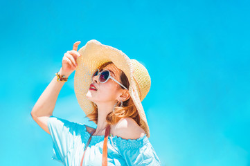 summer holidays, vacation, travel and people concept - smiling young woman in sun hat on beach over sea and blue sky background.?jump on the beach.copy space