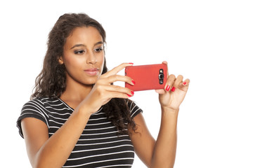 Young and happy dark skinned girl taking photos with her smartphone