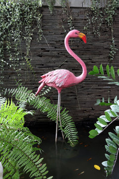 The pink stucco Flamingo in the the pond. Beautiful Pink Bird Statue standing in the pond at the garden.