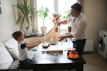 boy and dad roll out dough in cozy real interior