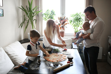 parents with two children prepare pizza in cozy