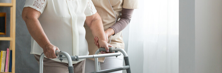 Assistant supporting elderly woman