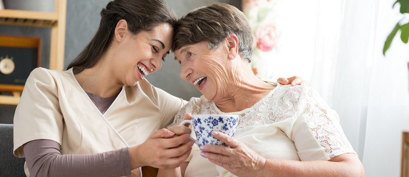 Nurse and laughing senior woman