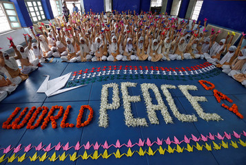 Students hold paper cranes during International Peace Day in Ahmedabad