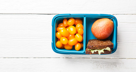 Image of cherry tomato, pear, sandwich in lunchbox