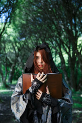Photo of witch in cloak with book