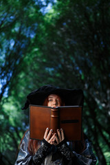 Portrait of witch with large spellbook