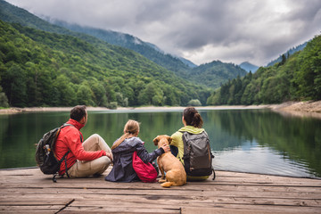 Family with dog resting on a pier