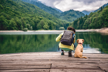 Woman with a dog standing on pier by the lake