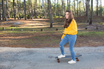 Brunette teenage girls hipster outfit with a skateboard at the park outdoors
