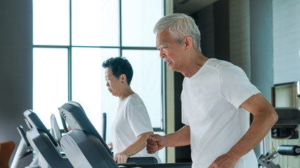 Healthy Asian senior couple exercise together in gym running treadmill
