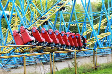 Red rollercoaster riding on blue and yellow railroad against blue sky in the summer amusement park
