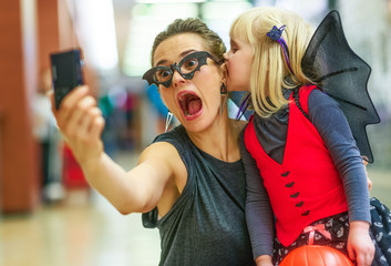 mother and daughter taking scary Halloween selfie on digital pho