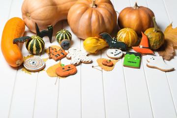 Halloween background with decorated gingerbread and autumn pumpkins.