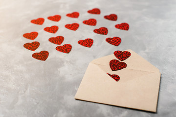 Envelope from craft paper with red hearts heap spread on grey background.