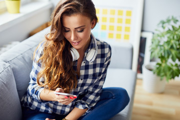 Portrait of a pretty smiling young woman sitting on sofa in living room and using phone