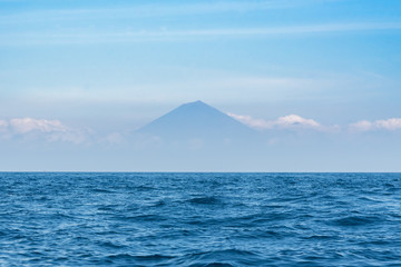 Blue ocean with clear sky and Agung mountain on background. Bali, Indonesia.